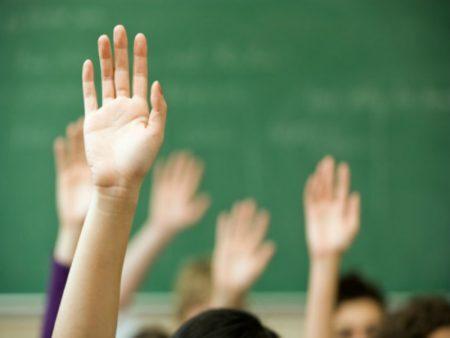 Alunos em sala de aula com mãos levantadas