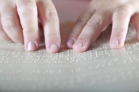 Mãos lendo braille