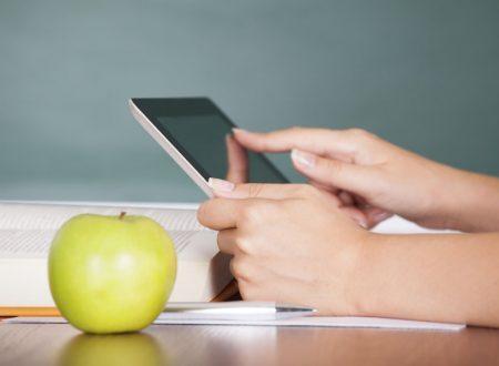 Pessoa mexendo no tablet e maçã à frente