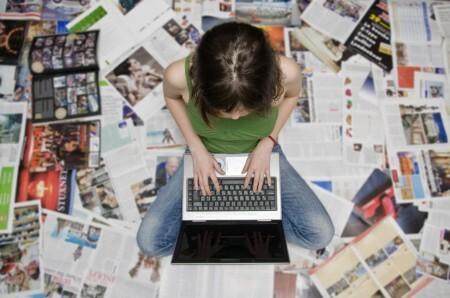Estudante com laptop e revistas ao redor