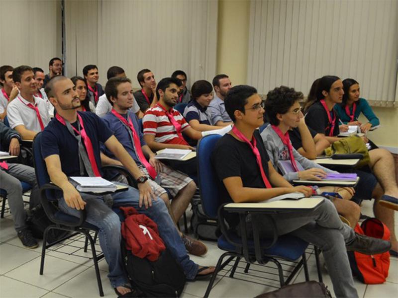 Estudantes durante a aula, usando gravatas rosas.