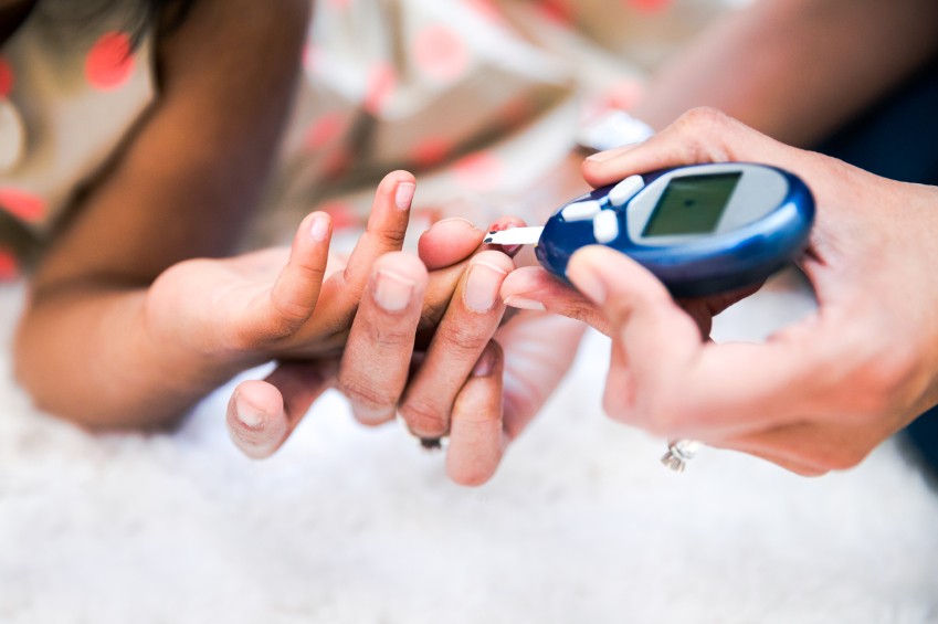 Mother is checking her daughters' diabetes by monitoring blood g