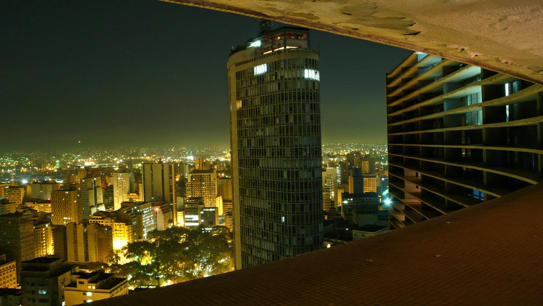 """Edifício Copan - O Edifício Copan, com sua inconfundível forma em """"S"""", é um dos principais cartões postais da cidade. Projetado na década de 1950 pelo grande expoente da arqui - tetura moderna brasileira, Oscar Niemeyer, com a cola - boração do arquiteto Carlos Lemos, foi inaugurado em 1966. Da cobertura do prédio tem-se uma impactante vista da urbanidade da região central da cidade."""