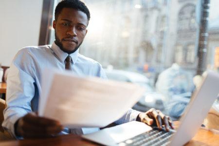 advogado negro lendo papeis na frente do notebook