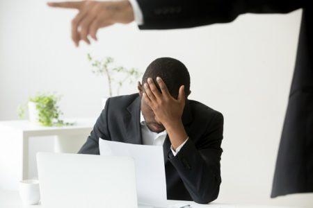 homem negro com a cabeça baixa, frustrado, sendo humilhado por um homem branco em caso de racismo no trabalho