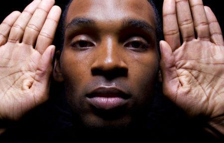 foto de homem negro com as mãos espalmadas ao lado de seu rosto