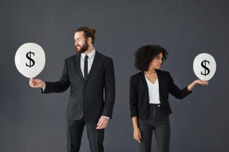 machismo no mundo dos negócios: casal segurando duas bexigas simbolizando seus salários: a mulher está com a bexiga menor que a do homem