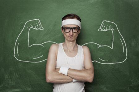 homem magro e nerd com roupa de academia em frente a uma lousa com braços musculosos desenhados