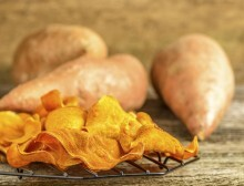 Freah homemade sweet potato chips on a rustic background.