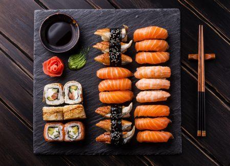 Sushi Set sashimi and sushi rolls on black stone slate