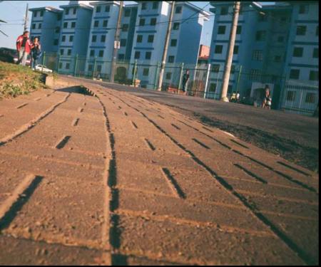 imagem de baixo para cima de uma calçada de paralelepípedos ao fundo prédios e pessoas andando