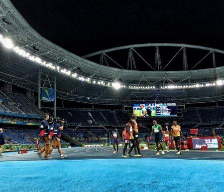 Imagem da pista de atletismo do estádio do Engenhão. Em primeiro plano o chão azul claro e logo atrás a pista de atletismo com os atletas , deficientes visuais e seus guias , logo após a linha de chegada da prova dos duzentos metros rasos. São 4 atletas com seus guias. Ao fundo mais acima as luzes do estádio estão acesas e céu escuro da noite.