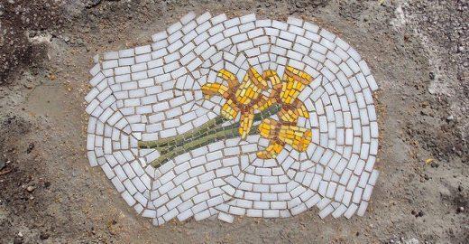 Artista usa flores para tapar e denunciar buracos na cidade