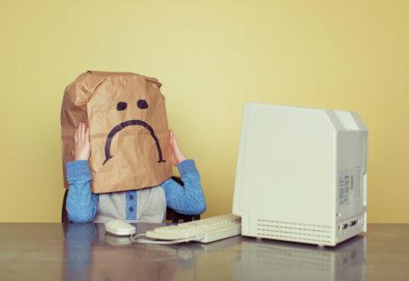 menino triste com saco de papel na cabeça sofrendo cyberbullying