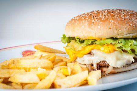 Os hambúrgueres podem vir acompanhados de batatas fritas ou onion rings - porção de anéis de cebola empanados e fritos