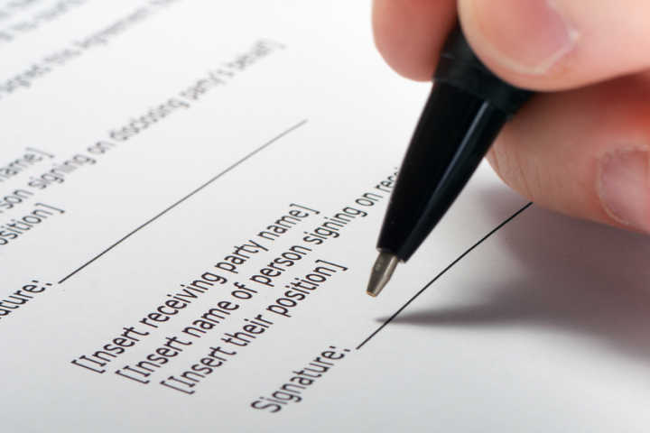 Businessman's hand signing papers. Lawyer, realtor, businessman sign documents on white background. Copy space for text