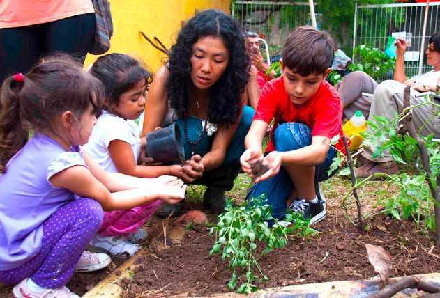 Crianças aprendendo a importância de respeitar a natureza em evento na praça