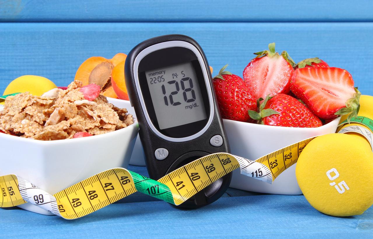 Medidor de glicose com o nível de açúcar, alimentos saudáveis, halteres e fita métrica