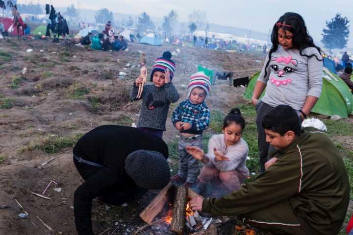 Família tenta se aquecer em campo de refugiados na Grécia