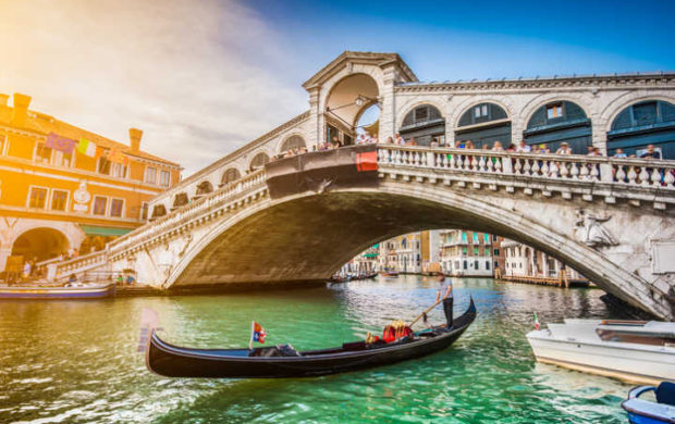 Beautiful view of traditional Gondola on famous Canal Grande with Rialto Bridge at sunset in Venice, Italy with retro vintage Instagram style filter and lens flare effect.