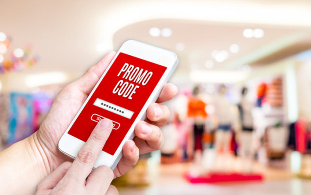 Hand holding mobile phone with promo code word