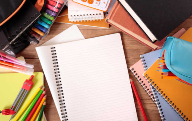 Busy student's desk with blank folded notebook