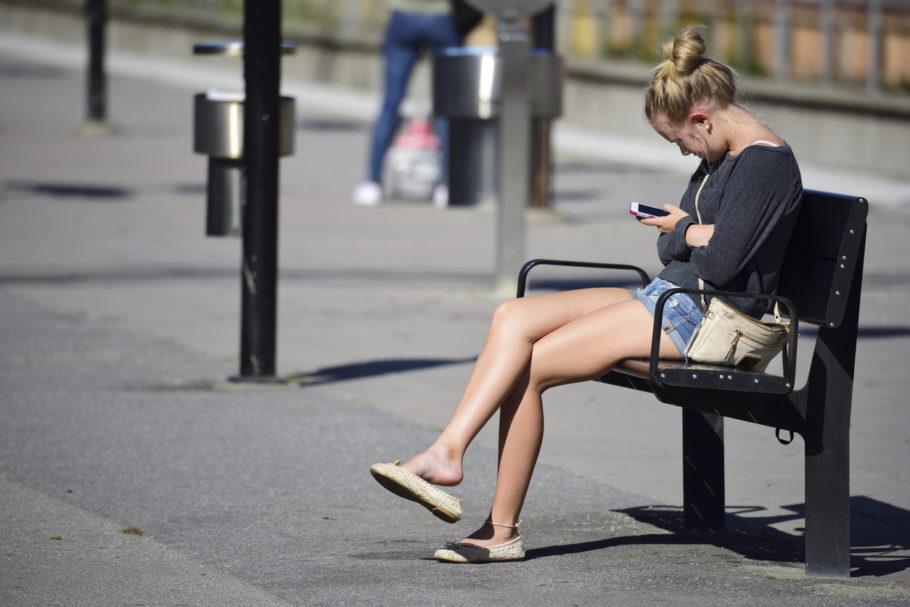 mulher com a cabeça inclinada usando o celular