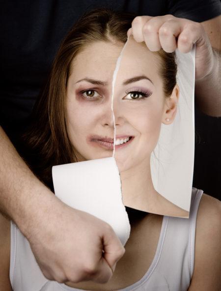 mulher agredida com o olho roxo atrás de uma foto sua rasgada sorrindo