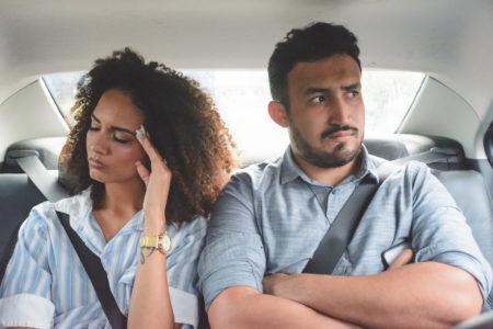 mulher evitando contato visual com homem dentro de um táxi