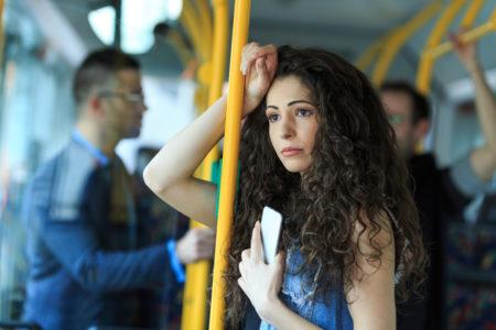 mulher assediada no transporte público olhando para a janela
