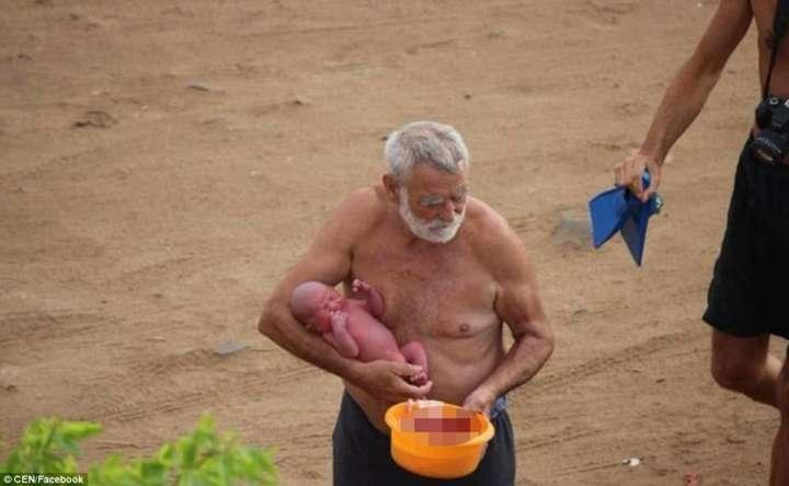 Avô segura o bebê ainda com o cordão umbilical