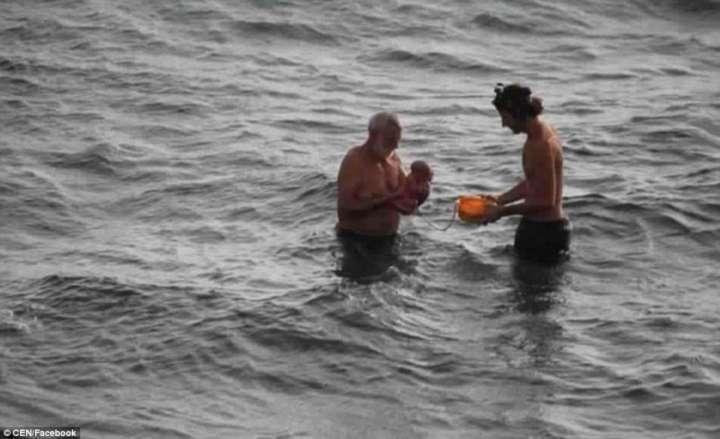 Avô e pai tiram a criança do mar após o parto
