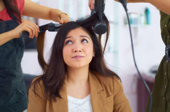 Mulher com chapinha e secador no cabelo