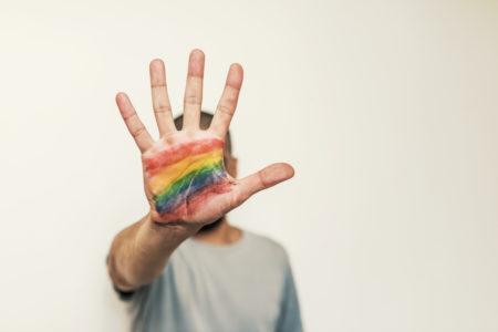 homem mostrando a palma da mão com a bandeira lgbt desenhada
