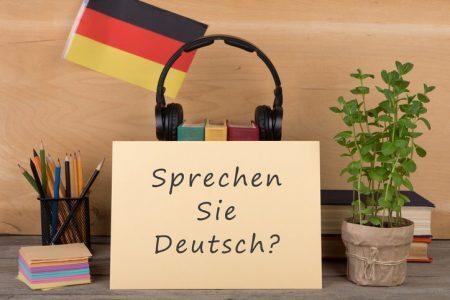 """Papel com texto """"sprechen sie deutsch?"""" e bandeira da Alemanha"""