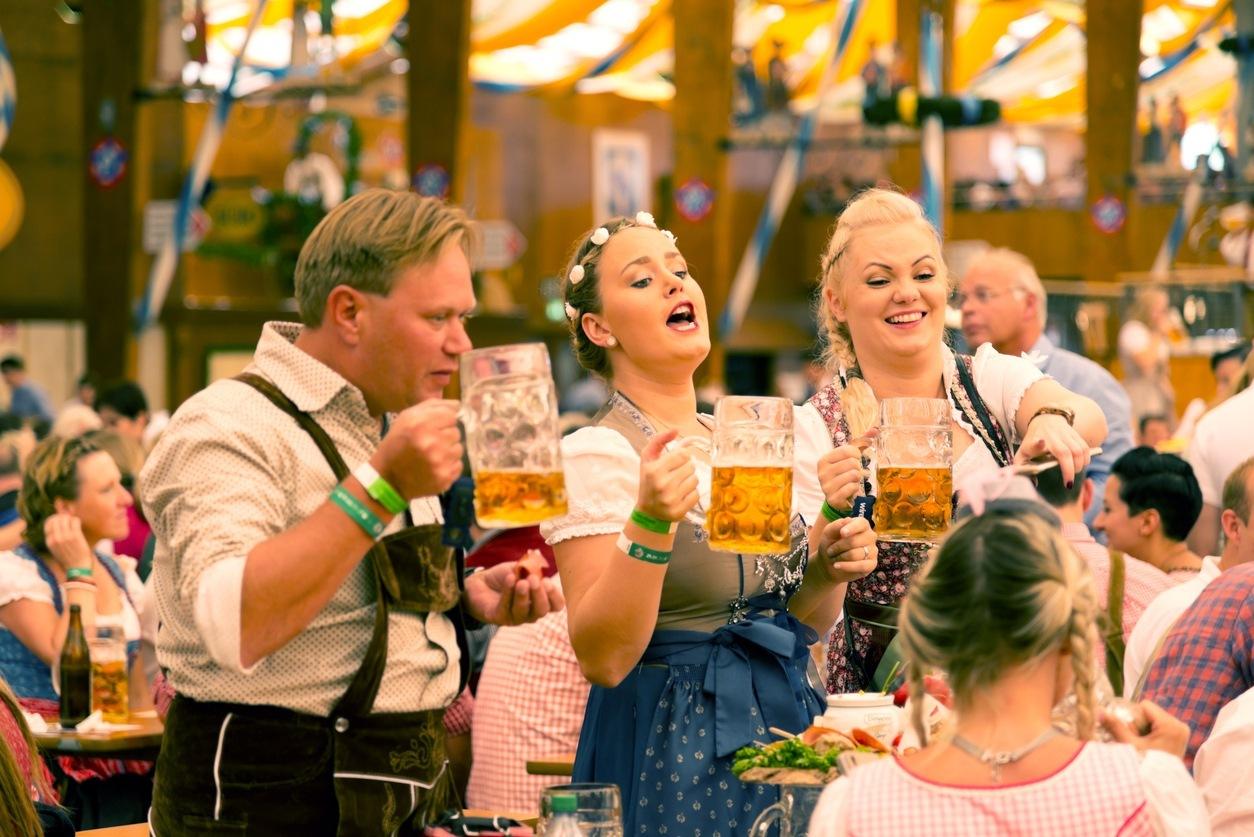 Jovens bebem cerveja com roupas típicas alemã na Oktoberfest, em Munique
