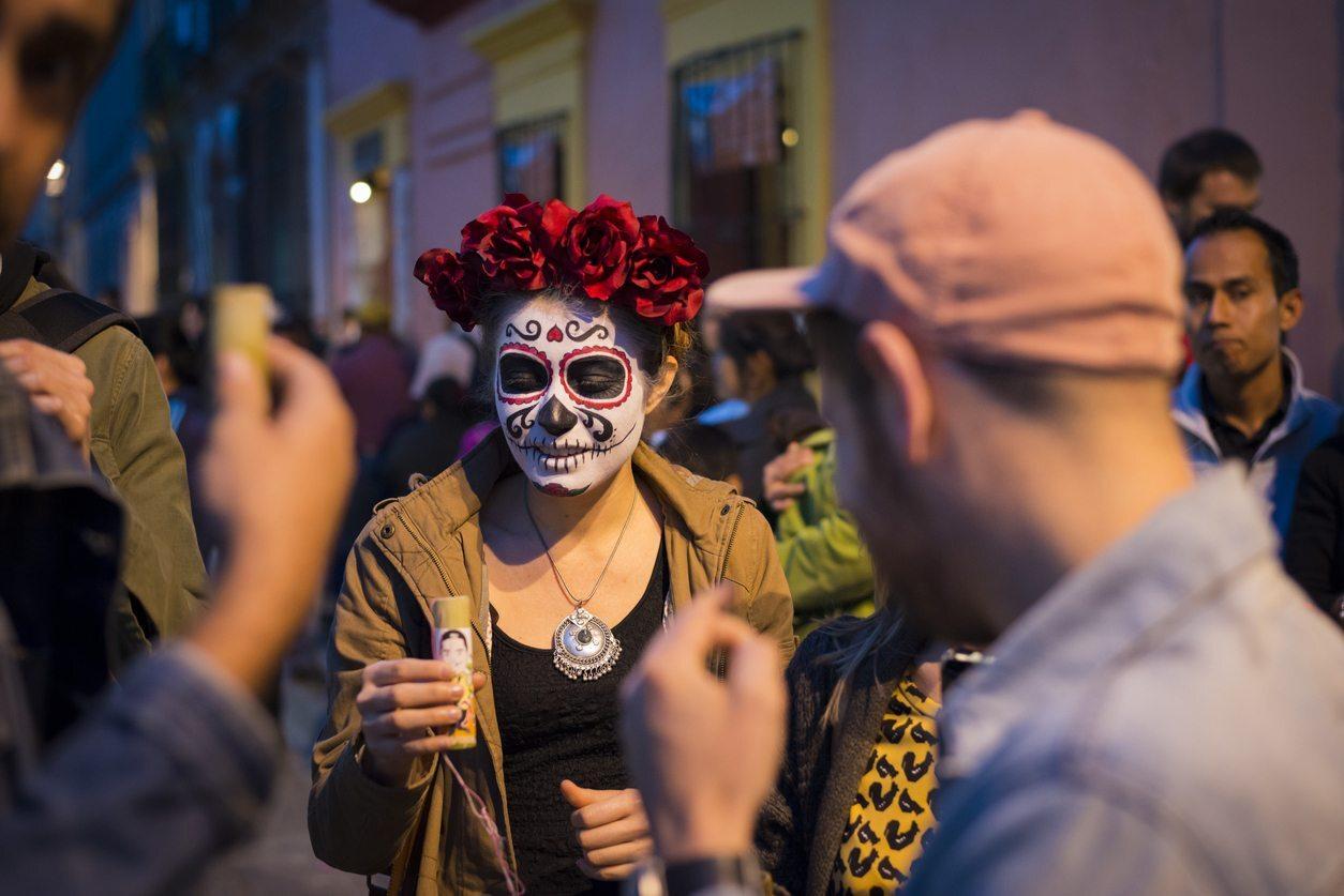 Jovem bebe tequila na festa do Dia de los Muertos em Oaxaca