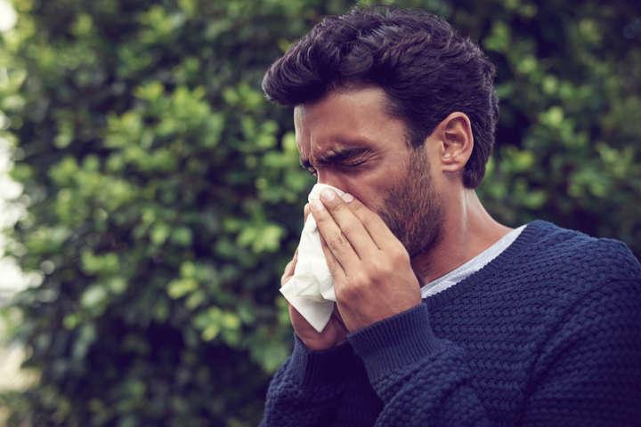 Homem com lenço de papel assoando o nariz