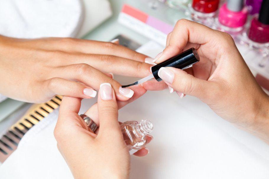 Unhas sendo pintadas com esmalte incolor por manicure