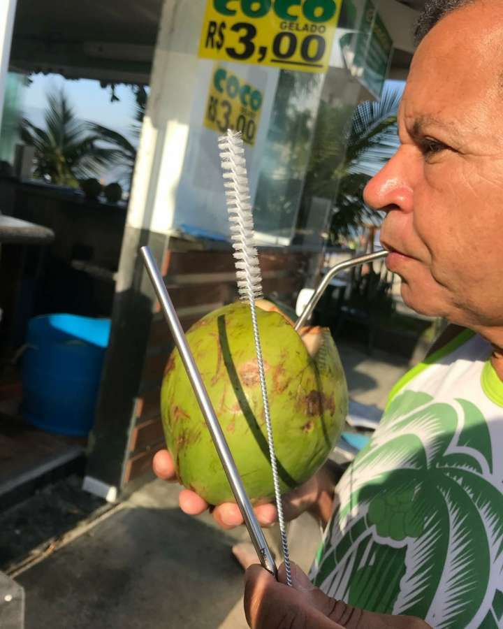 Zé do Coco, dono do quiosque, toma água de coco com canudo de aço