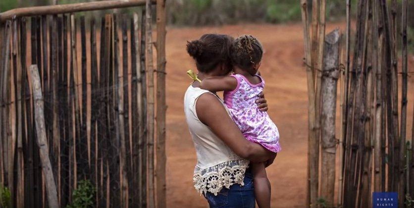 mulher com criança no colo em zona rural