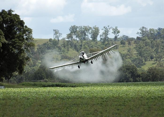 avião jogando agrotóxicos em uma plantação