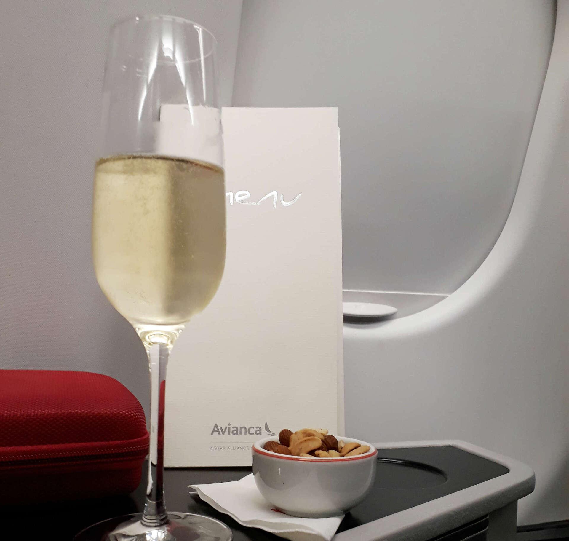 Passageiros recebem uma taça de espumante de boas-vindas na classe executiva da Avinca