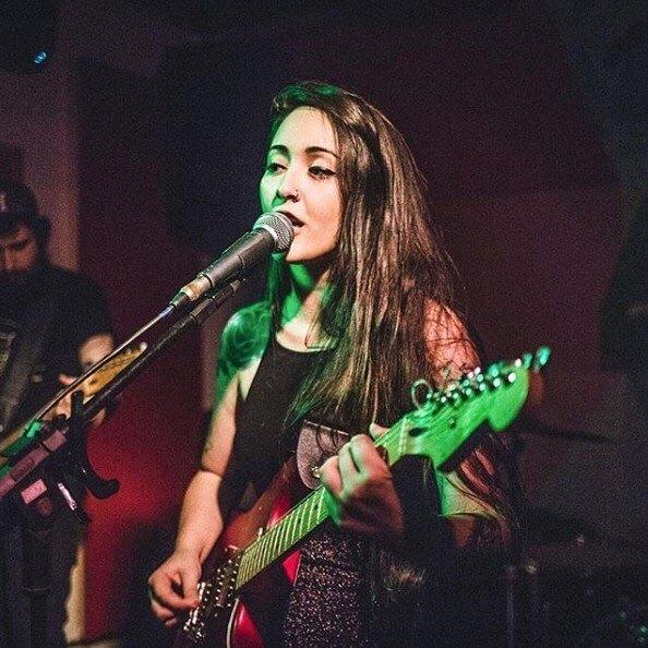 Foto da cantora Bruna Guimarães no palco tocando guitarra