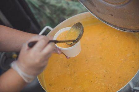 Foto em close de uma panela de caldo de milho com uma pessoa servindo em um potinho