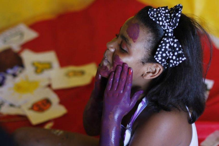 Menina negra se pinta de roxo
