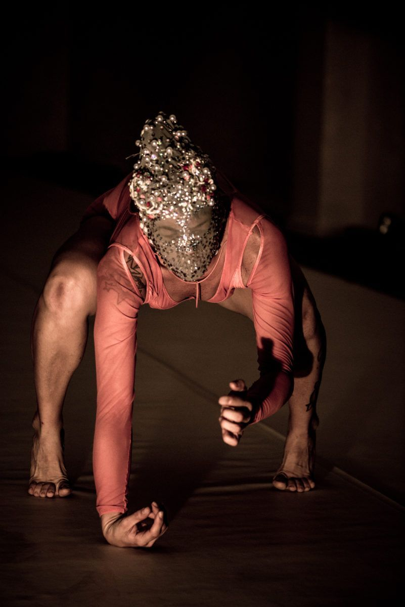 Bailarina agachada, com máscara na cabeça