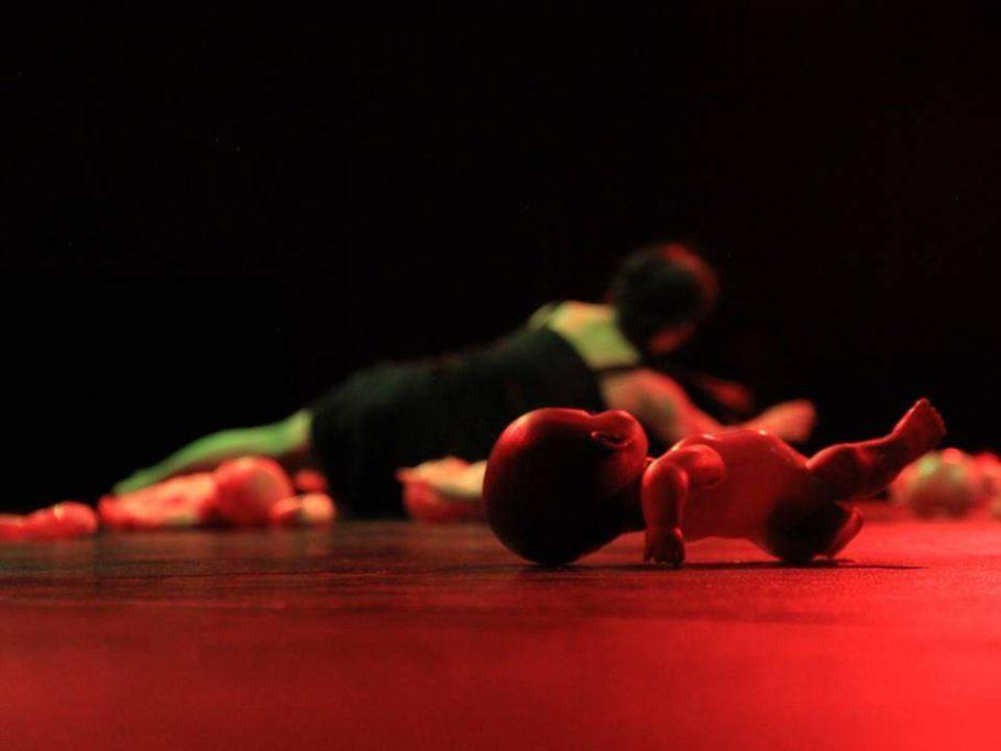 """Foto do espetáculo """"Con La boca bien abierta"""", em que uma bailarina e diversas bonecas estão deitados no palco"""