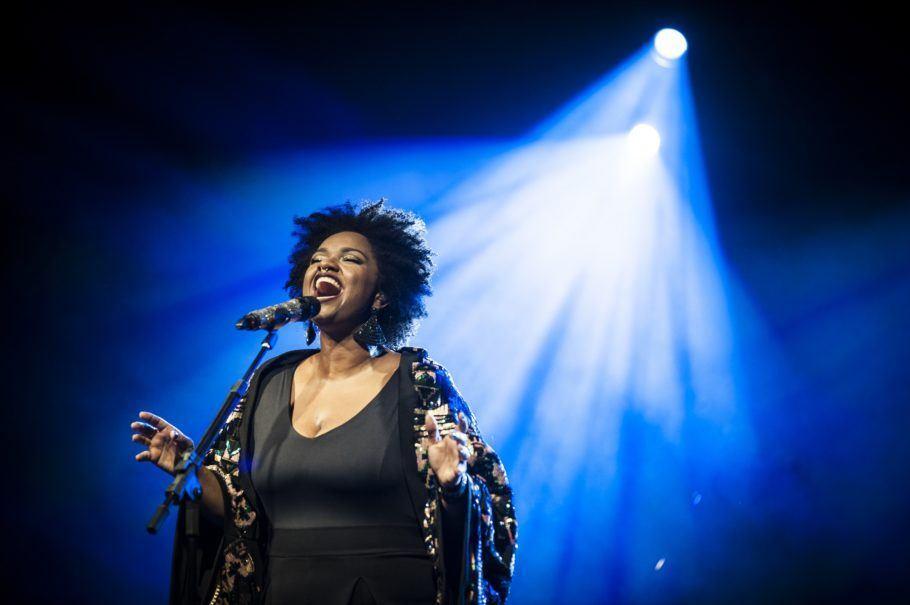 Cantora Ellen Olélia no palco com uma luz azul incidindo sobre ela