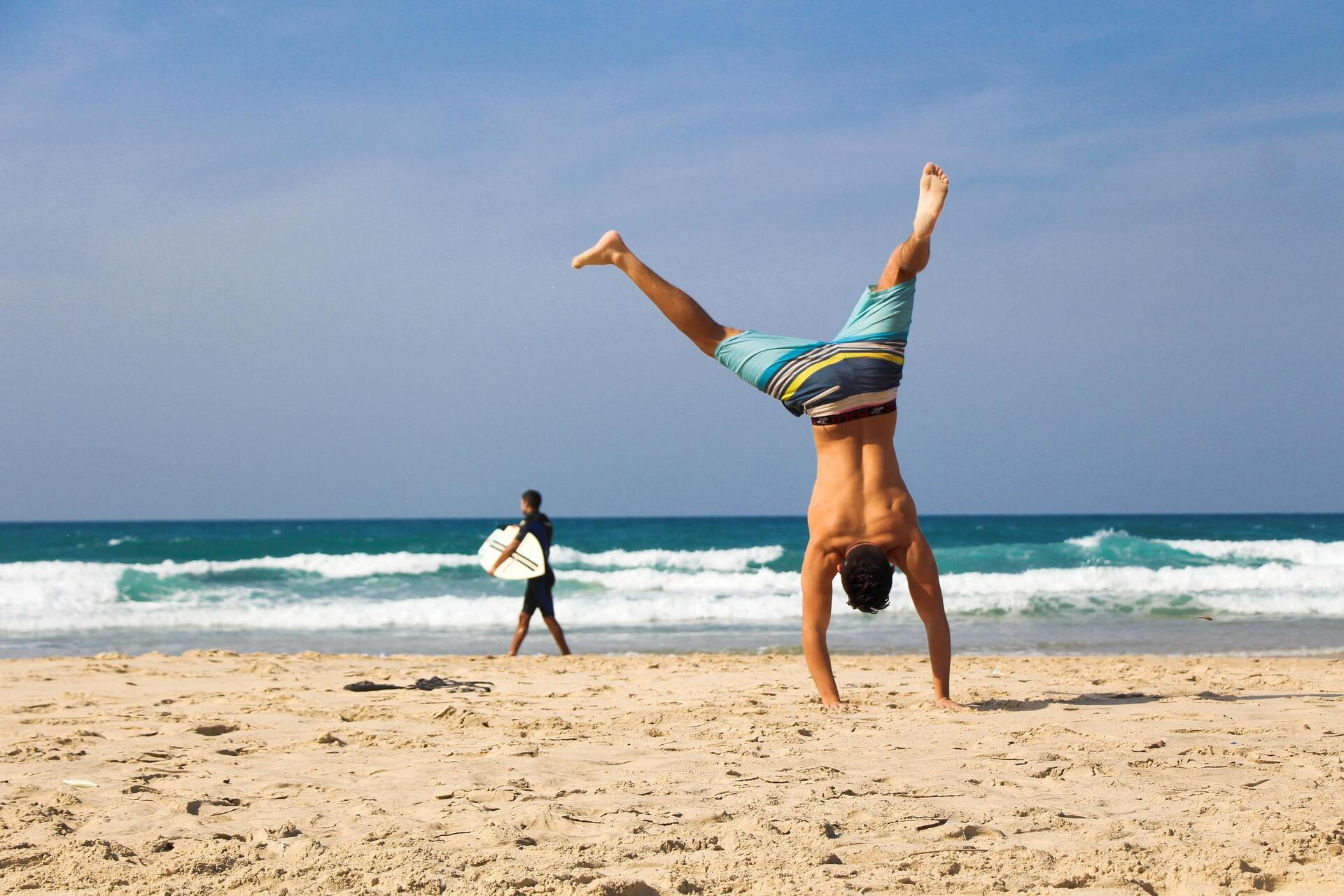 jovem dando estrelas na areia da praia